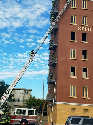 Recruit Training - image of active drill with aerial ladder extended to training tower